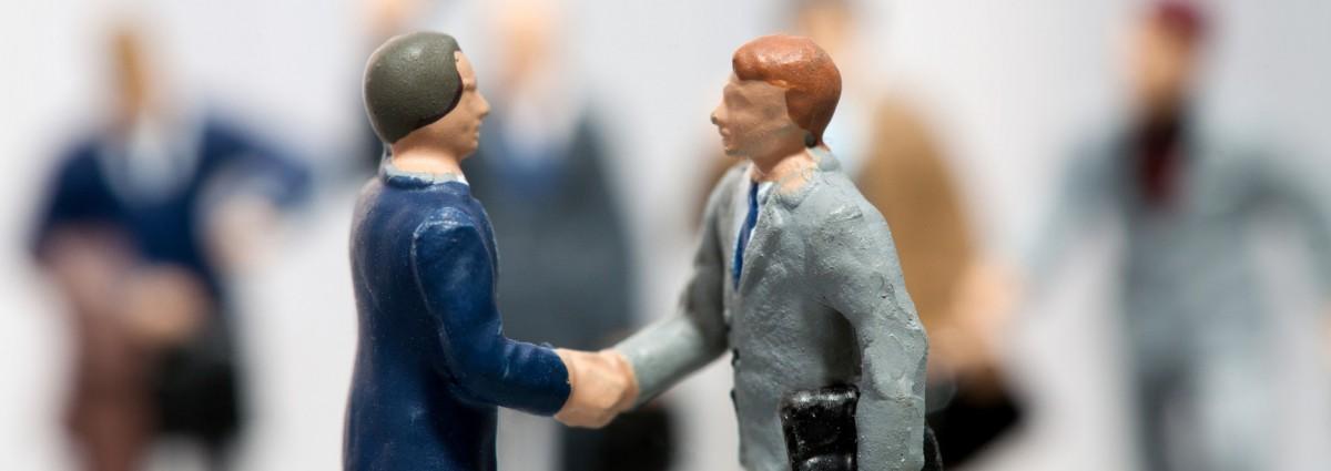 Miniatur Geschäftsmänner schütteln Hände